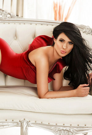 Dark haired London escort in a red velvet dress lying on a sofa